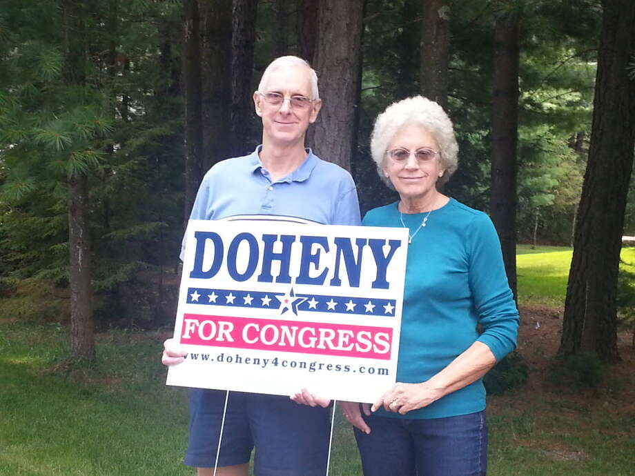 Peter and Peg Jasinski, standing in front of their Queensbury home, hold one of the political signs that led to a clash with the Hudson Pointe Homeowners Association. (Photo by Chris Churchill / Times Union)