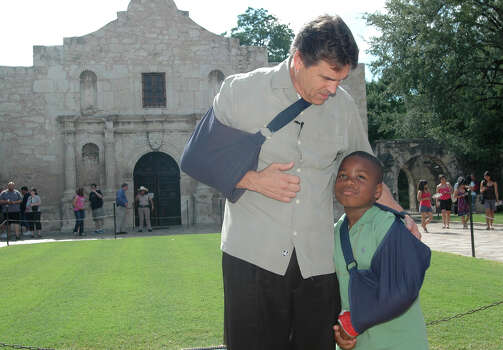 Gov. Rick Perry talks with Devin Lacy, 7, who broke his wrist on a trampoline, after signing legislation in front of the Alamo on June 15, 2009. Photo: BETH SPAIN, San Antonio Express-News / Copyright 2009