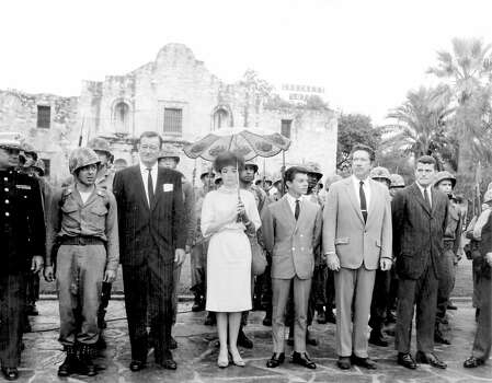 """Cast members of the 1960 film """"The Alamo,"""" including (from left of the helmeted soldier) John Wayne, Linda Cristal, Frankie Avalon, Richard Boone and Pat Wayne, pay tribute to the fallen defenders of the Alamo during a ceremony on Alamo Plaza on Oct. 24, 1960, the morning of the world premiere of the film. Photo: San Antonio Express-News File Photo"""