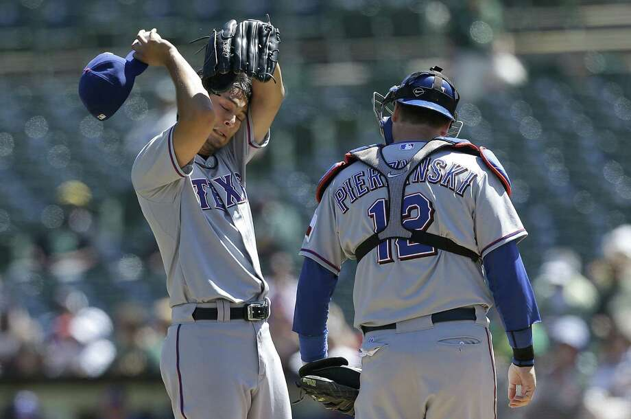Rangers pitcher Yu Darvish wipes his brow during a visit from catcher A.J. Pierzynski in the first against the Athletics. Two of the five runs Darvish allowed in his five-plus innings came in the frame. Photo: Jeff Chiu / Associated Press