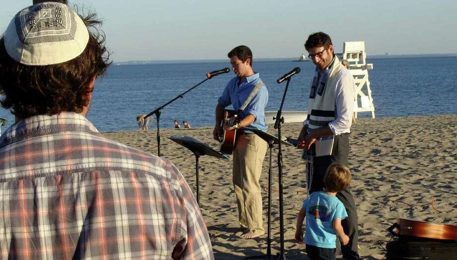 Rabbi Evan Schultz, right, and Michael Creager, a student at Western Connecticut State University, lead the Congregation B'nai Israel's first Rosh Hashana sunset service at Jennings Beach on Wednesday to welcome the New Year.   FAIRFIELD CITIZEN, CT 9/4/13 Photo: Meg Barone / Fairfield Citizen contributed