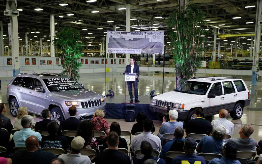 FILE - In this Aug. 13, 2013 file photo, Scott Garberding, senior vice president of manufacturing for Chrysler Group LLC stands between a 1992 Grand Cherokee, right, and the automaker's 5,000,000th vehicle produced at the Jefferson North Assembly Plant in Detroit. Chrysler's U.S. sales rose 12 percent in August as strong truck sales pushed the company to its best month in six years. Photo: Carlos Osorio