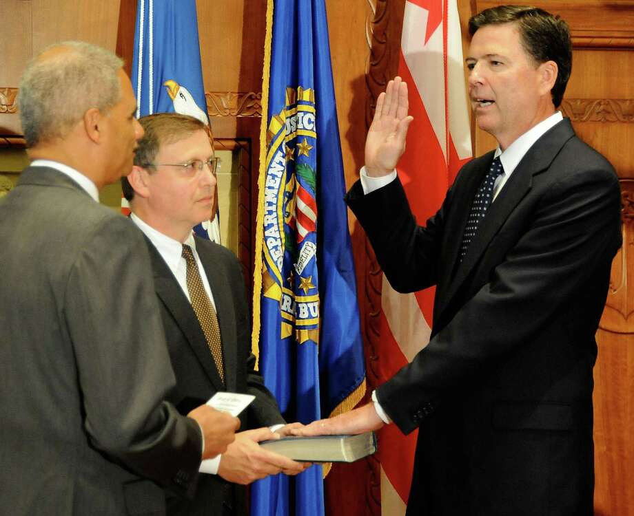 James B. Comey of Westport, right, is sworn in as FBI director Wednesday by U.S. Attorney General Eric Holder. Chuck Rosenberg, senior counselor to Comey, holds the Bible. Photo: FBI / Westport News