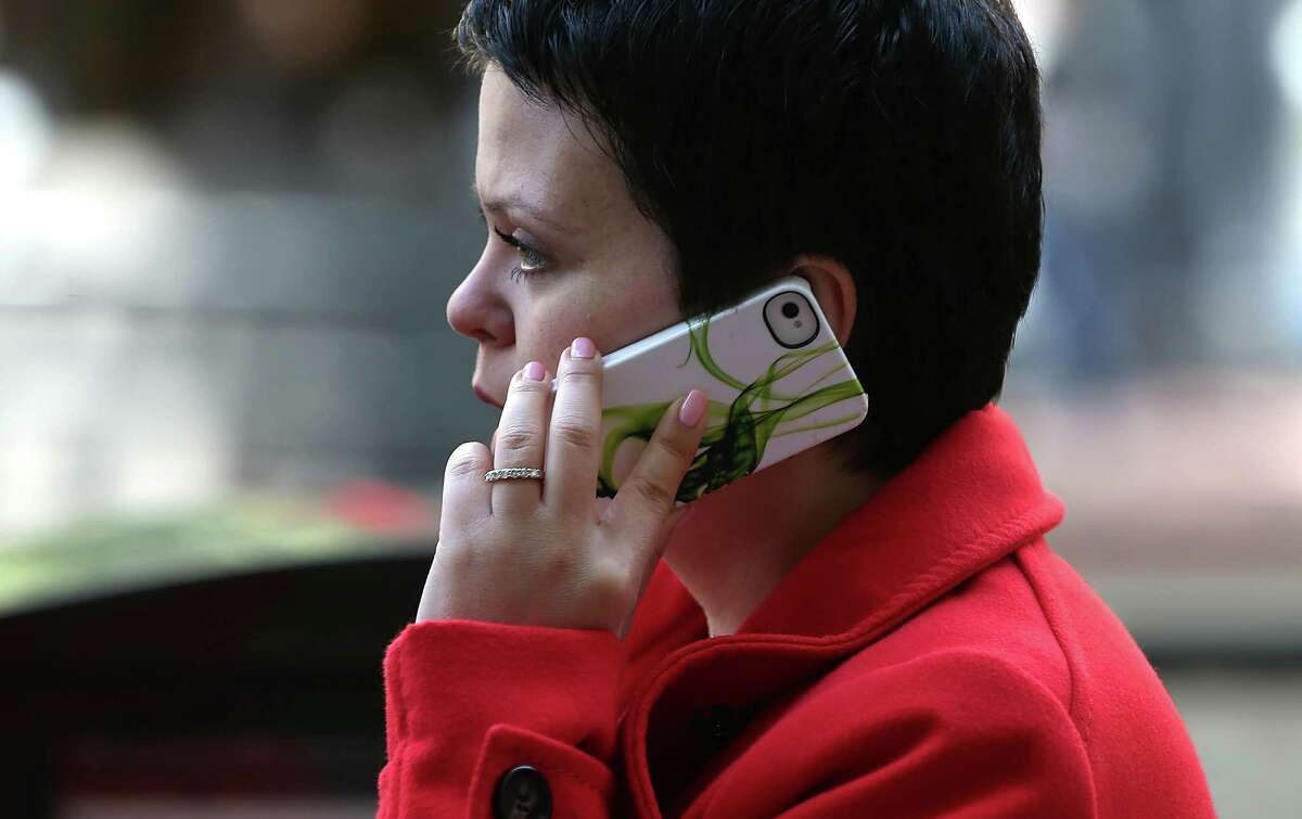 A pedestrian talks on an iPhone as she walks along Market Street on June 5, 2013 in San Francisco, California. According to an estimate by YouMail, Inc., Americans received 29.3 billion robocalls in 2016.