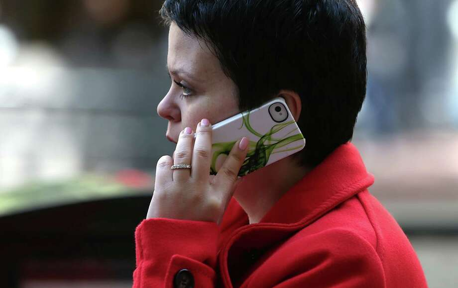 A pedestrian talks on an iPhone as she walks along Market Street on June 5, 2013 in San Francisco, California. According to an estimate by YouMail, Inc., Americans received 29.3 billion robocalls in 2016. Photo: Justin Sullivan, Getty Images / 2013 Getty Images