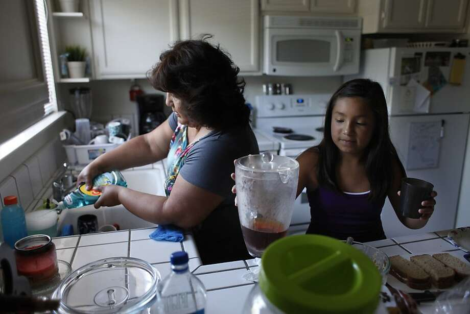 Dora Andrade (left), washing dishes as granddaughter Alexia Andrade grabs a drink, wants to live a healthier lifestyle. Photo: James Tensuan, SFC