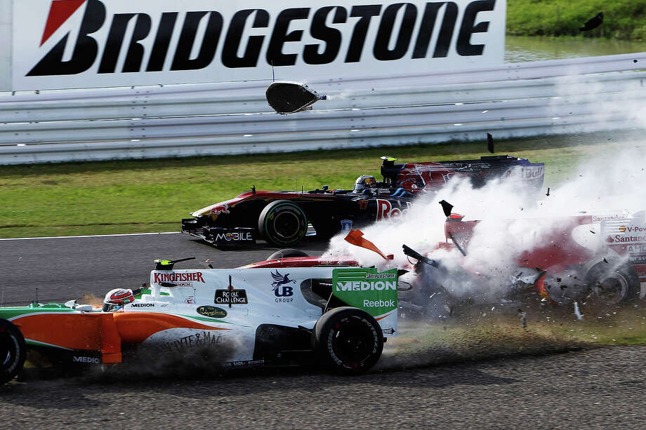Felipe Massa (red) of Brazil and Ferrari and Vitantonio Liuzzi (white) of Italy and Force India crash at the first corner at the start of the Japanese Formula One Grand Prix at Suzuka Circuit on October 10, 2010 in Suzuka, Japan. Photo: Hoch Zwei, Getty Images / 2010 Hoch Zwei