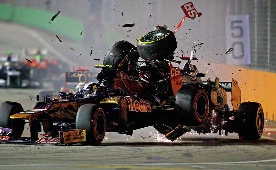 Michael Schumacher (R) of Germany and Mercedes GP crashes with Jean-Eric Vergne of France and Scuderia Toro Rosso during the Formula One Grand Prix of Singapore at Marina Bay Street Circuit on September 23, 2012 in Singapore. Photo: Vladimir Rys Photography, Getty Images / 2012 Vladimir Rys