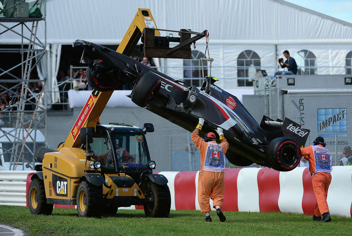 A crane lift Esteban Gutierrezs Sauber car at the end of the Canadian Formula One Grand Prix at the Circuit Gilles Villeneuve in Montreal, June 9, 2013. A race-track worker at the Canadian Grand Prix was killed after he slipped under the wheel of the crane, officials said, as he was escorting the crane as it moved Esteban Gutierrez's Sauber car following a crash.