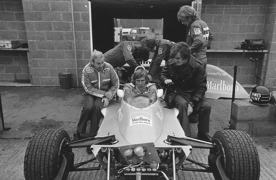 British racing driver James Hunt sitting at the wheel of the M26 Marlboro McLaren racing car at Silverstone. Teddy Mayer, racing director sits to his left, and team manager Alistair Caldwell is on the right. Photo: Sydney O'Meara, Getty Images / Hulton Archive