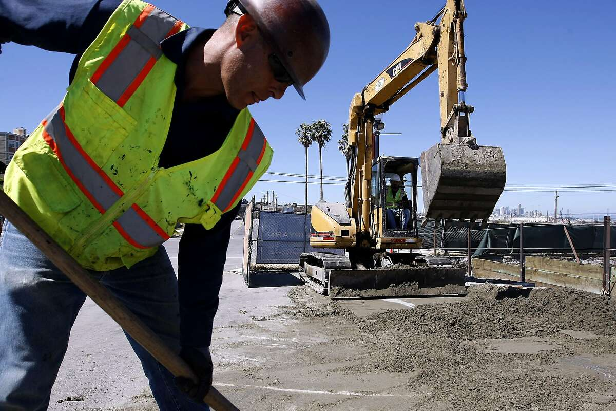 Manuel Cuevas with Ranger Pipeline shovels dirt while Angelo Gonzales operates a backhoe as construction gets under way at the Shipyards project in Hunter's Point, San Francisco, CA Wednesday September 4, 2013.