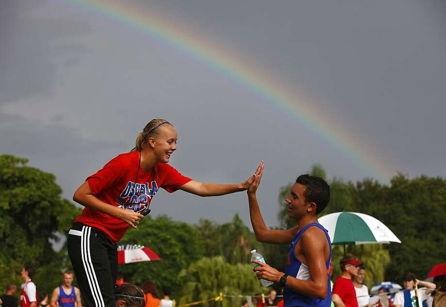 Meanwhile, birds burst into song: After completing the 5k race at the Green Devil Invitational in St. Petersburg, Fla., Osceola High runner Justice Galaris receives a high-five from fellow schoolmate Maddy Repka as a rainbow forms. Photo: Lara Cerri, Associated Press