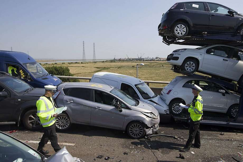 Big pileup in the English fog:Police examine wreckage after more than 100 vehicles crashed   on the Sheppey crossing bridge  in Sheppey, Kent. Thick fog was blamed for the chain-reaction collisions that left eight people seriously hurt and 60 with minor injuries. Photo: Justin Tallis, AFP/Getty Images