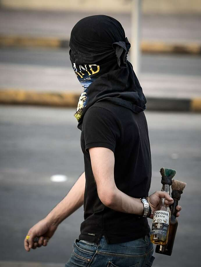 That's not lime in his Corona:A Bahraini protester prepares to hurl Molotov cocktails   at riot police following an anti-regime demonstration near Manama. The   rally was sparked by the death of Sadeq Sabt, 22, who was fatally injured when he   was hit by a vehicle during a protest a month before. Photo: Mohammed Al-Shaikh, AFP/Getty Images