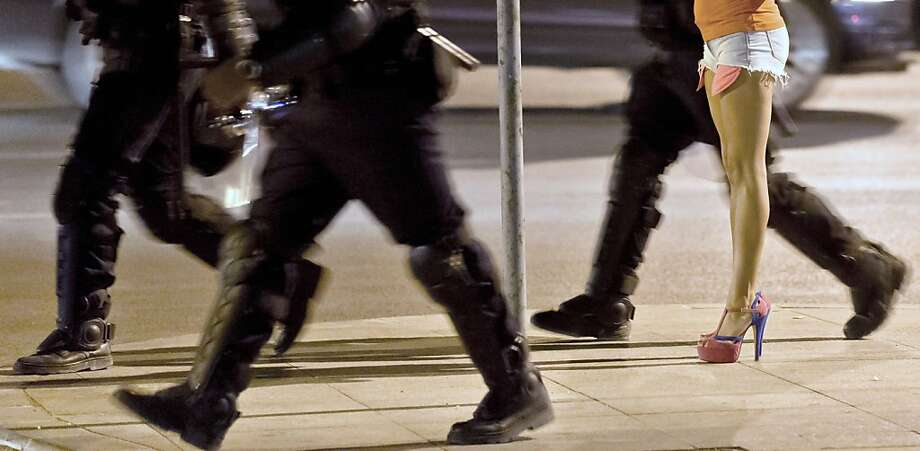 Pardon us, Miss: Romanian riot policeman stride down a Bucharest street to confront protesters gathering 