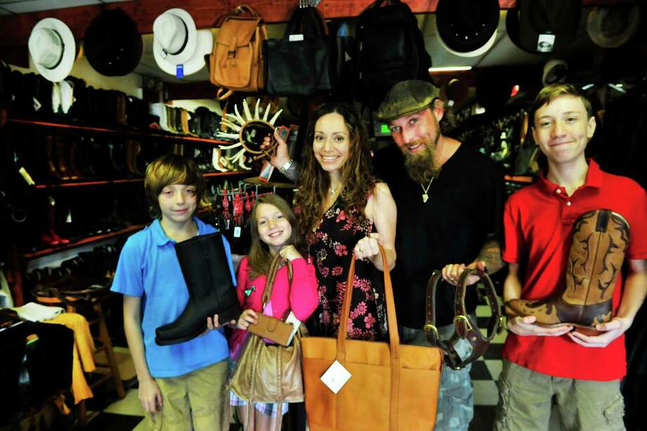 The Wellers stand inside Leather J's, their new shop in New Milford, Conn. Thursday, Sept. 5, 2013. From left are Noah, 13; Cheyenne, 10; Vanessa; Jason; and their son, Jason, 14. Photo: Michael Duffy / The News-Times