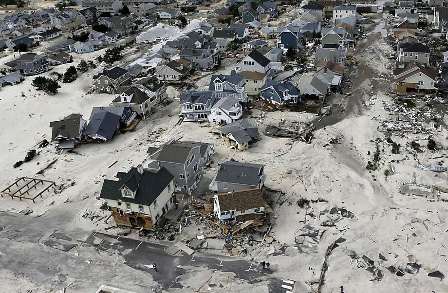 FILE - In an Oct. 31, 2012, file aerial photo, the destroyed and damaged homes are left in the wake of Superstorm Sandy in Ortley Beach, N.J. Researchers with the United States and British governments concluded Thursday Sept. 5, 2013, that climate change had made these events more likely: U.S. heat waves, Superstorm Sandy flooding, shrinking Arctic sea ice, drought in Europe's Iberian peninsula, and extreme rainfall in Australia and New Zealand. (AP Photo/Mike Groll, File) Photo: Mike Groll, Associated Press
