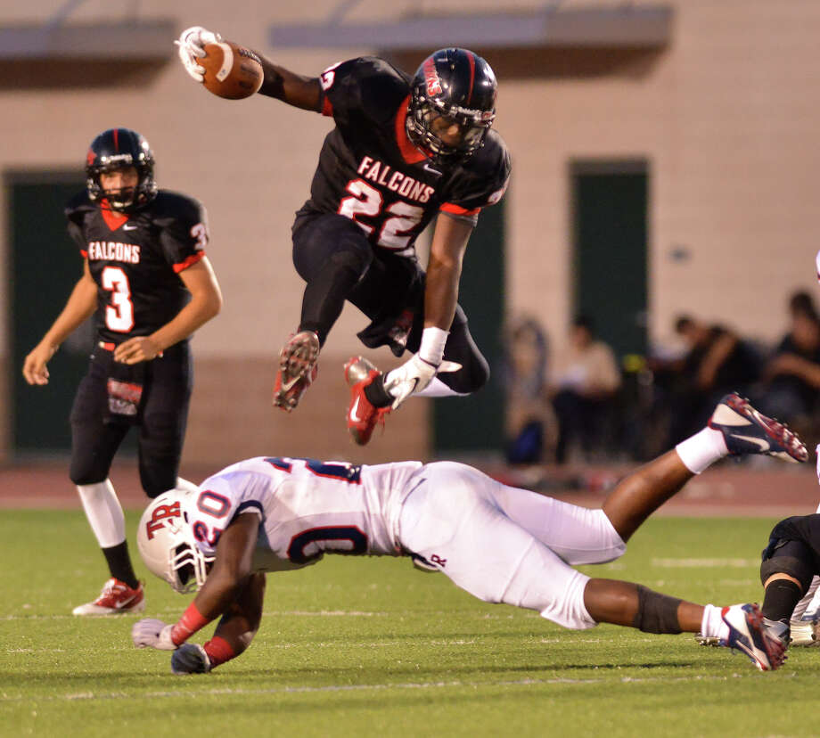 Stevens High School running back Marquie Hinton jumps over Roosevelt's Victor Hunter during first half action. Photo: Robin Jerstad, San Antonio Express-News
