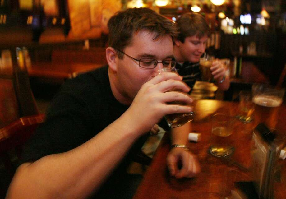 A couple of patrons chug some Irish Car Bombs at Brian O'Neill's in Rice Village.   Photo: Billy Smith II, Houston Chronicle