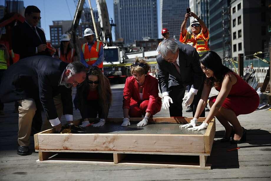 Michael Theriault (left), Maria Ayerdi-Kaplan, Nancy Pelosi, Ed Lee and Jane Kim make handprints in poured cement. Photo: Lea Suzuki, The Chronicle