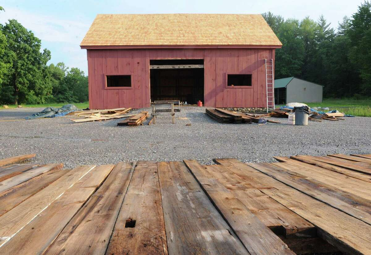 Barn wood lays on the ground in front of Peter Brooks's barn on Tuesday, June 25, 2013 in Malta, N.Y. Wood has been installed in the 200-year-old barn which is being put together with original materials. (Lori Van Buren / Times Union)