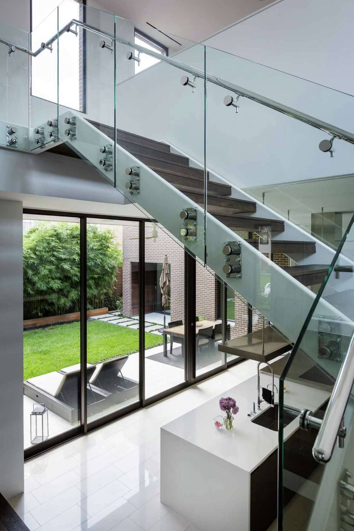 A stainless steel and wood tread staircase with glass railing contibutes to the open feeling of the layout. ( Michael Paulsen / Houston Chronicle )