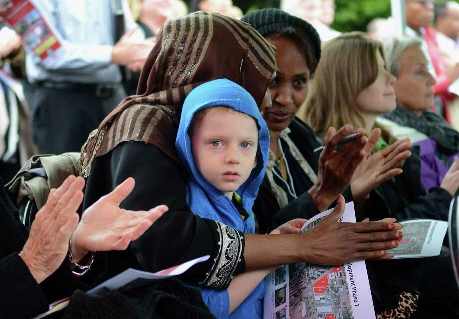 Community members clap after hearing speaches during the ground-breaking ceremony, September 5, 2013 at 11th Avenue and East Fir Street in Yesler Terrace. The community is one of the most ethnically diverse and economically challenged in Seattle. Photo: SY BEAN, SEATTLEPI.COM / SEATTLEPI.COM