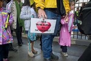 A father walks with his daughter to Marshall School on International Walk to School Day in San Francisco, Calif., on Wednesday, October 5, 2011.