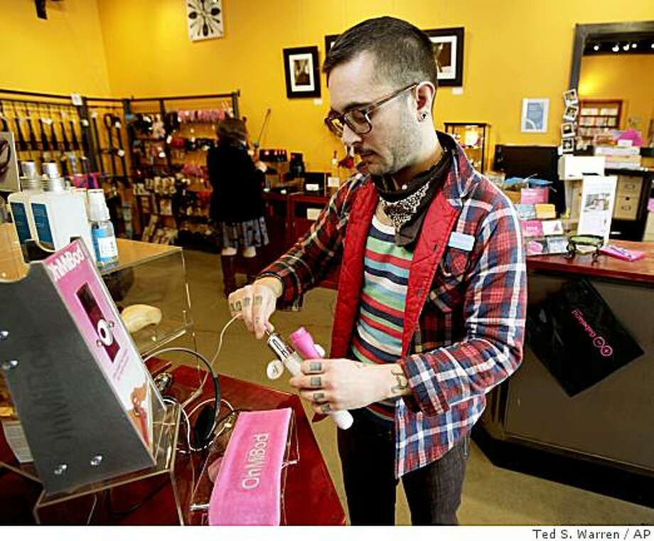 Inside Babeland in Seattle, which sells vibrators, lubricant, adult DVDs and other erotica. Store manager Kelly Arbor is pictured in 2009 as he changes the batteries of an adult toy that plugs into a mp3 music player. (AP Photo/Ted S. Warren)