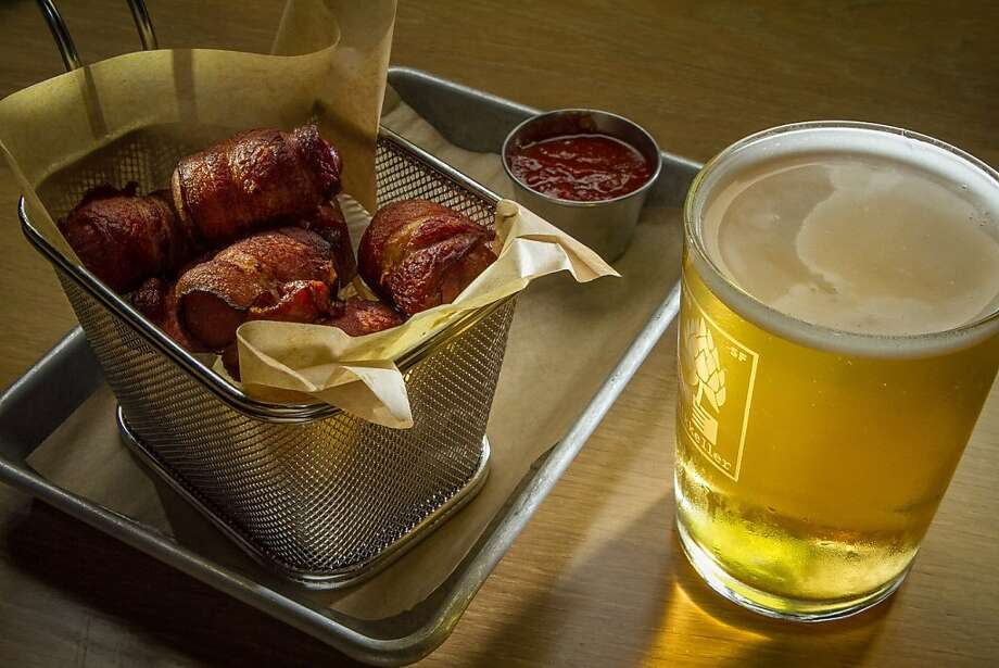 Lil' Smokies sausages ($10), with chipotle barbecue sauce, are served with an Upright Engelberg Pilsner at Mikkeller Bar. Photo: John Storey, Special To The Chronicle