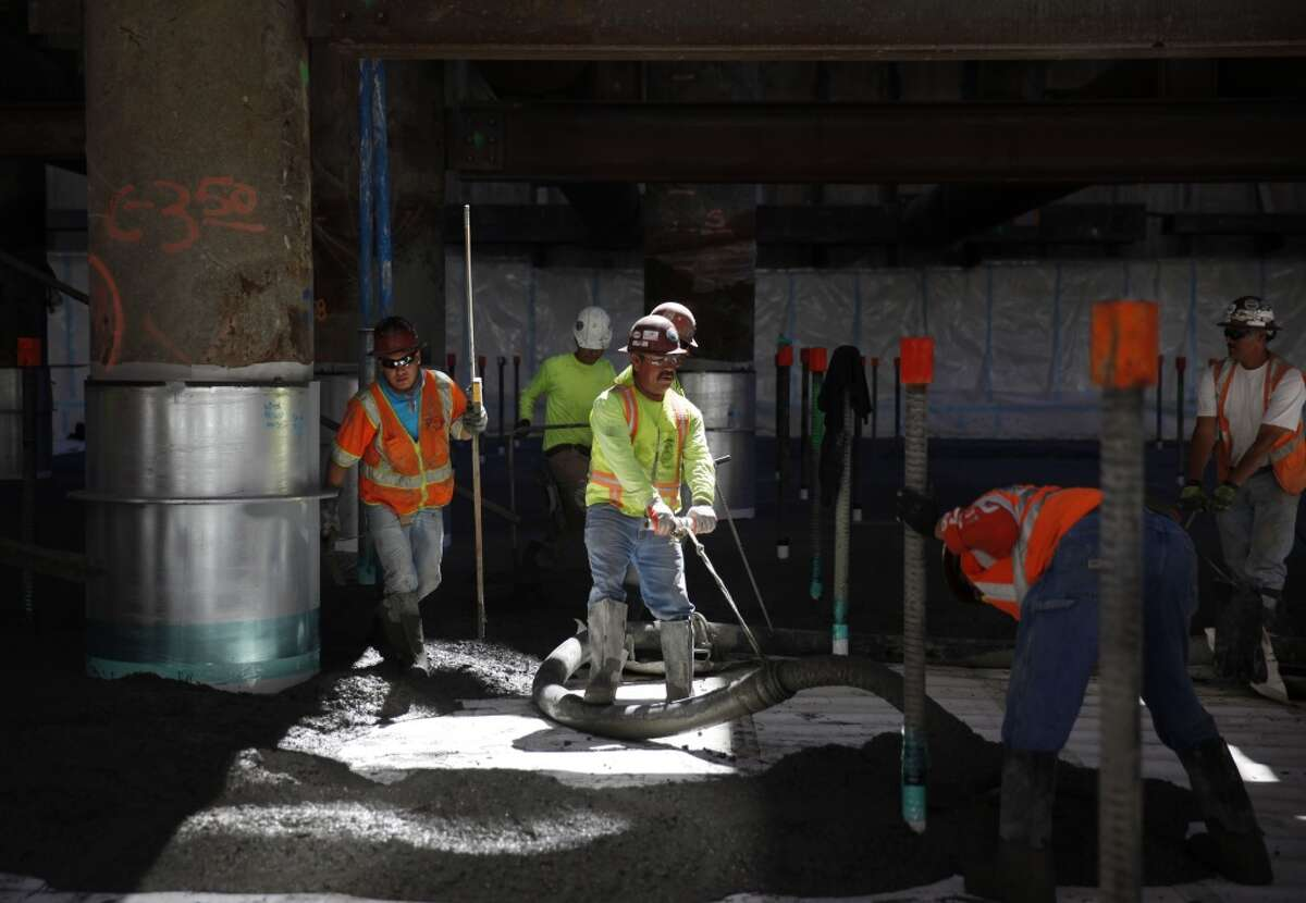 Workers work with oncrete being poured into a train box in Zone 2 for the future Transbay Transit Center's foundation on Thursday, September 5, 2013 in San Francisco, Calif.