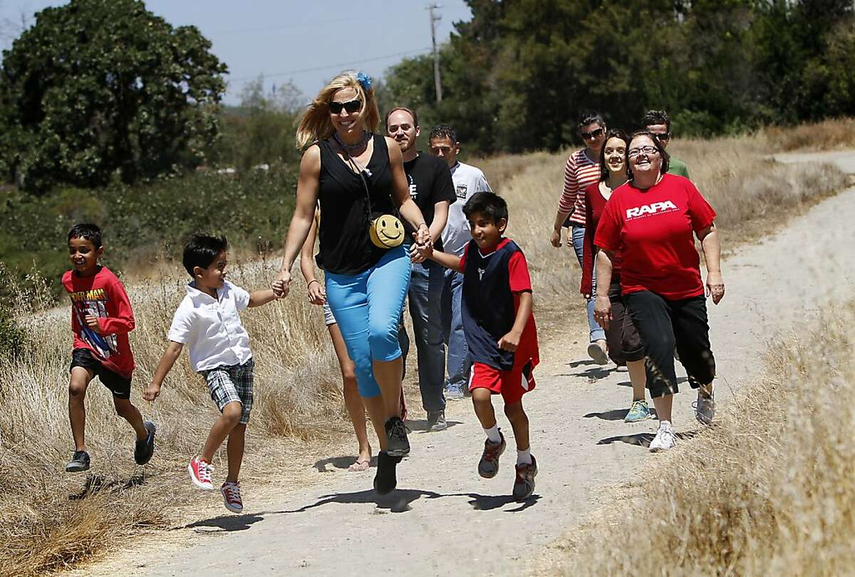 """Kim Corbin, of Novato, leads others in skipping on National Adult Skipping Day in Novato, Calif., Wednesday, July 31, 2013. Corbin has a new 21-day """"skipping for fun and fitness"""" action plan. She wants to get adults to skip a little every day, to take the childhood skip and bring it to people of all ages."""