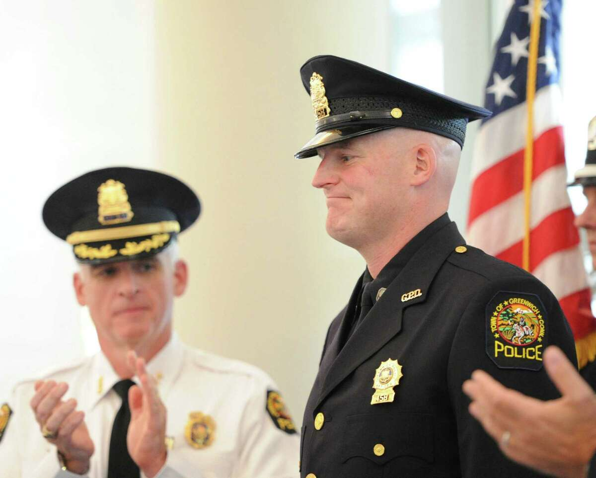 At left, Greenwich Police Chief James Heavey applaudes just after Greenwich Police Officer Ernest Mulhern, right, was promoted to rank of Sergeant during a ceremony at Greenwich Police Headquarters, Thursday, Sept. 5, 2013.