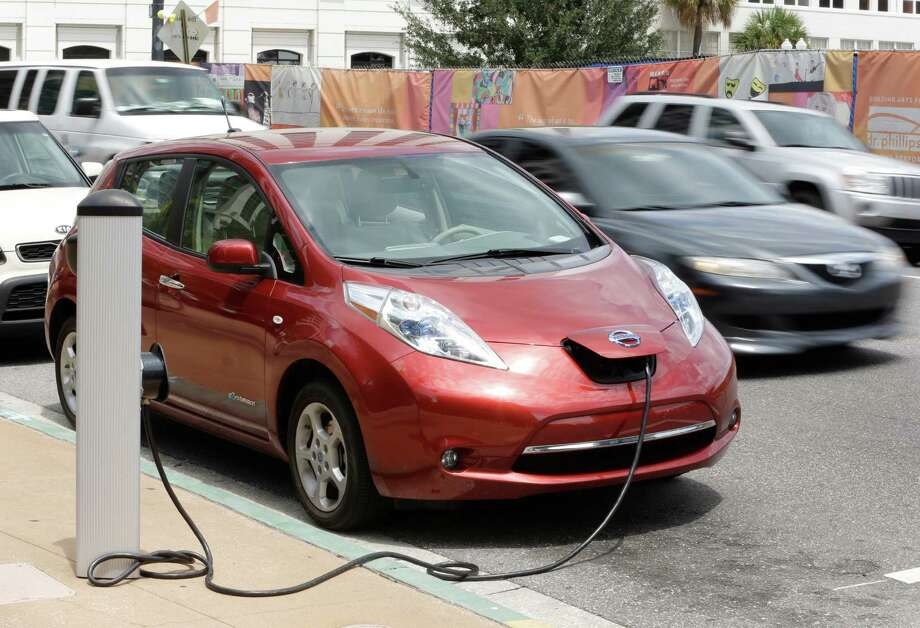 This Sept. 4, 2013 photo shows an electric car at a charge point in front of city hall in Orlando, Fla. On Thursday, Sept. 5, Orlando will be home to a first-of-its-kind electric rental car initiative where hotel partners will valet park the electric rental for free and charge it for you. Orlando already has more than 300 stations in the area. (AP Photo/John Raoux) ORG XMIT: FLJR107 Photo: John Raoux / AP