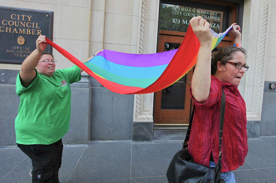 Jennifer Echeverry (left) and Julie Pousson celebrate with a rainbow flag Thursday Sep. 5, 2013, outside City Council chambers in Main Plaza after the council passed the nondiscrimination ordinance by a vote of 8-3. Photo: Edward A. Ornelas, San Antonio Express-News / © 2012 San Antonio Express-News