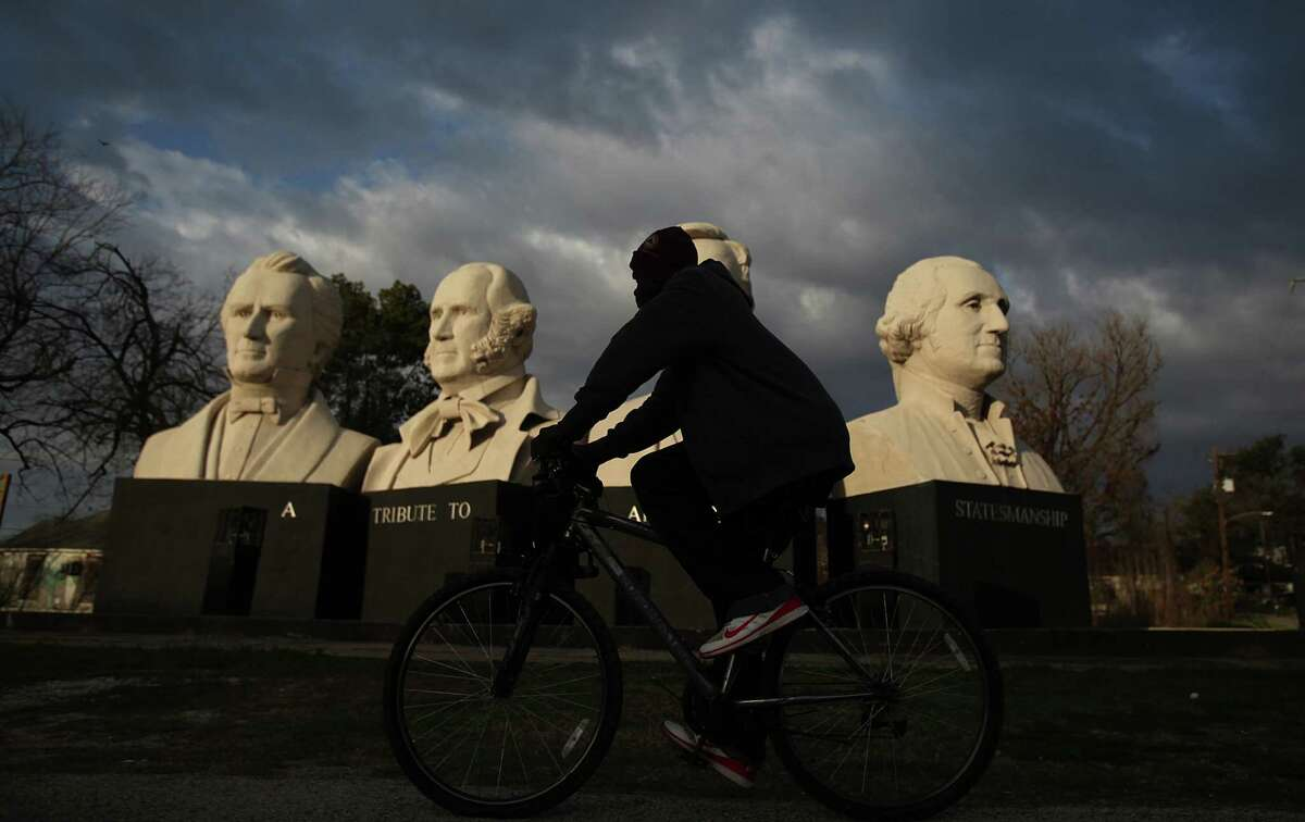 A cyclist pedals past the 18 foot tall concrete sculptures of Stephen F. Austin, Sam Houston, Abraham Lincoln and George Washington created by Houston artist David Adickes at American Statesmanship Park, also known as