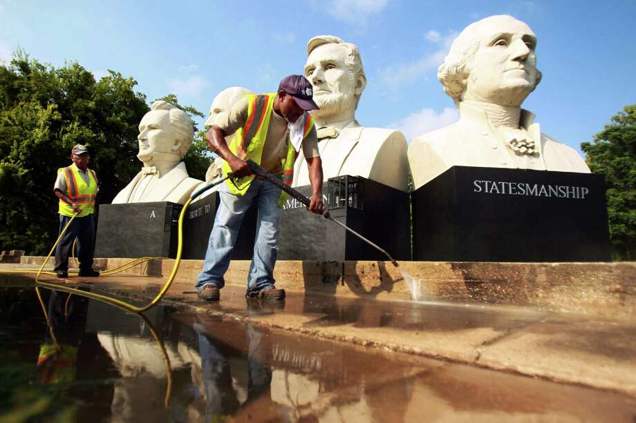 """Park worker Michael Caldwell power-washes the concrete under the busts, known collectively as """"Mount Rush Hour."""" Photo: Mayra Beltran, Staff / © 2013 Houston Chronicle"""