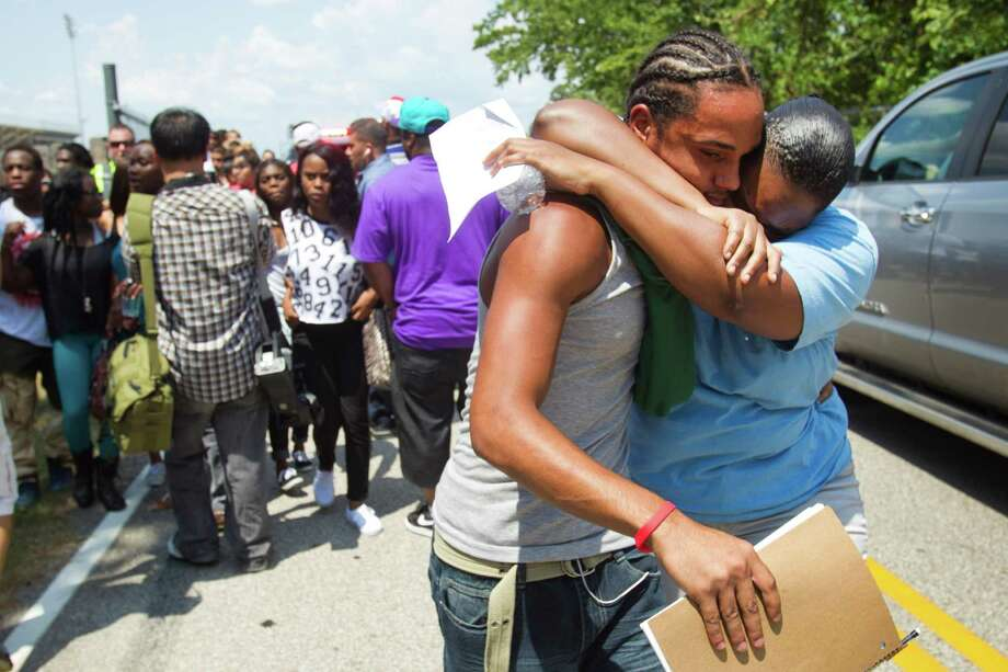A student is reunited with a loved one following a stabbing incident at Spring High School Wednesday, Sept. 4, 2013, in Spring. A student was stabbed to death and three others are injured after a fight at suburban school. Photo: Brett Coomer, Houston Chronicle / © 2013 Houston Chronicle