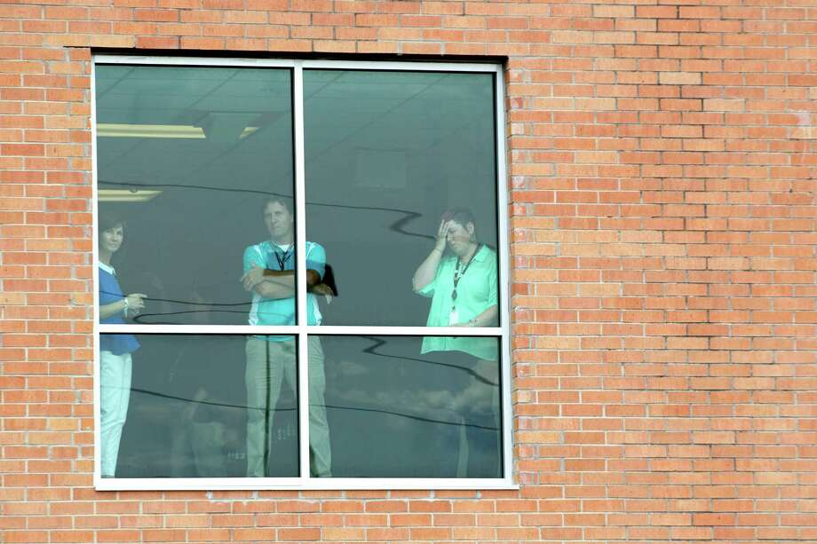 Staff members stand in a window following a stabbing incident at Spring High School Wednesday, Sept. 4, 2013, in Spring. A student was stabbed to death and three others are injured after a fight at suburban school. Photo: Brett Coomer, Houston Chronicle / © 2013 Houston Chronicle