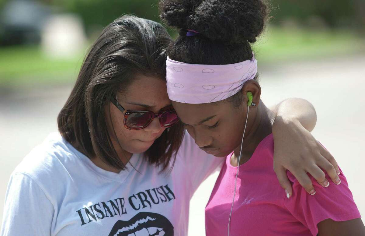 Khristian Friels, left, 17, a senior at Spring High School, hugs Destiny Barber, 14, a freshman, after attending a counseling session at the school on Thursday.