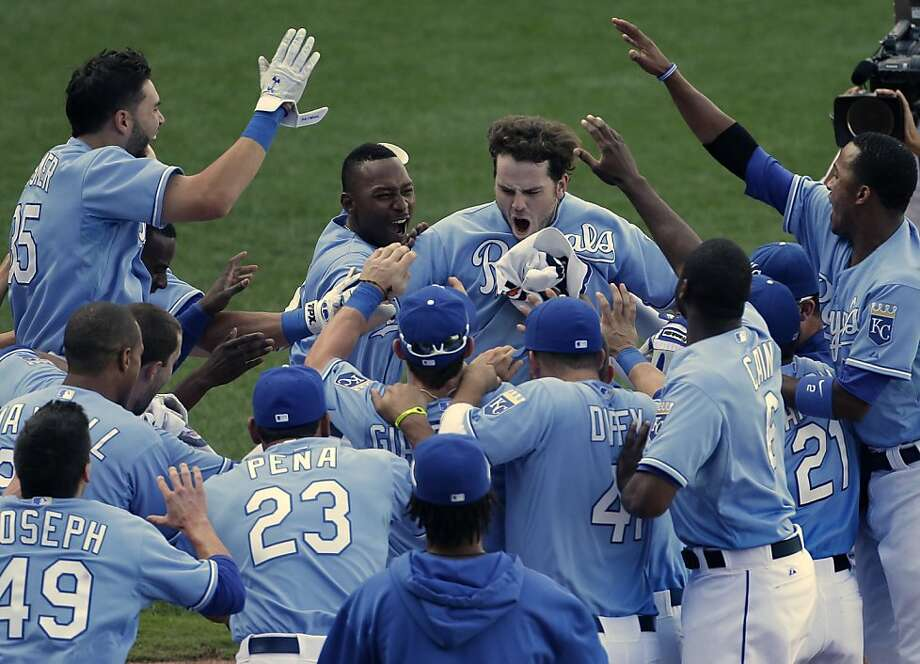 Kansas City Royals' Mike Moustakas, center, celebrates with his teammates after hitting a solo home run to win the game during the 13th inning of a baseball game against the Seattle Mariners Thursday, Sept. 5, 2013, in Kansas City, Mo. The Royals won the game 7-6. (AP Photo/Charlie Riedel) Photo: Charlie Riedel, Associated Press
