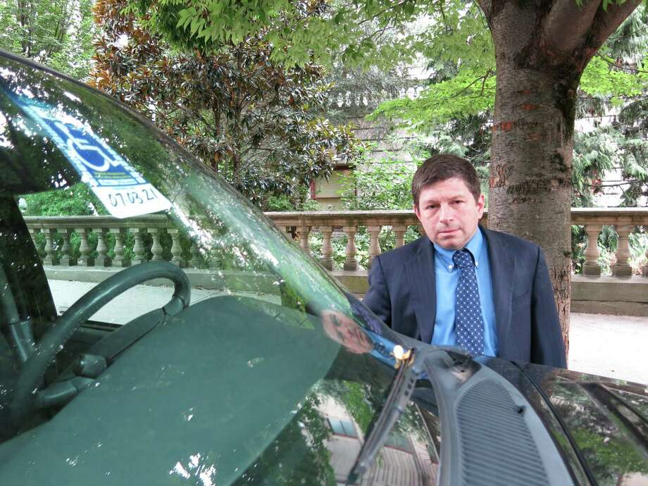 Portland, Ore., city commissioner Steve Novick stands next to a car in downtown that uses a disabled placard to park for free without a time limit on Thursday, Sept. 5, 2013, in Portland, Ore. Those cars stay all day long, costing the city meter revenue while reducing the turnover that shop owners like to see. Portland officials are now looking to charge disabled people who are not in wheelchairs for parking. Photo: Nigel Duara