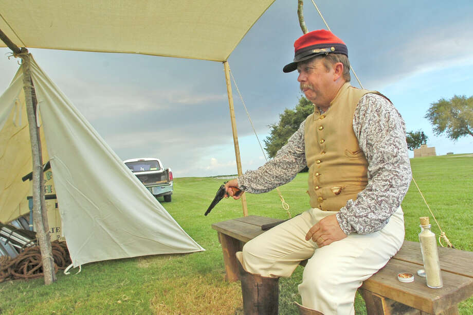 Donald Smart, who is the Commander of the Dick Dowling Camp as well as the weekend safety officer, test fires one of the caps in his unloaded 44 caliber army revolver underneath one of the set up tents on the Union side.   Later, he will fill the chambers with black powder, Cream of Wheat cereal, and hair spray to hold everything in place for the cap to ignite. The annual Dick Dowling Days held at the Sabine Pass battleground in Sabine Pass, will see some 300 plus re-enactors taking part this weekend in re-creating the Battle of Sabine Pass, which took place 150 years ago.  It is a two day event and the public is invited to walk through life as it was in 1863, see period camps, witness battle reenactments with canon fire, and cavalry   charges. The  Dave Ryan/The Enterprise Photo: Dave Ryan