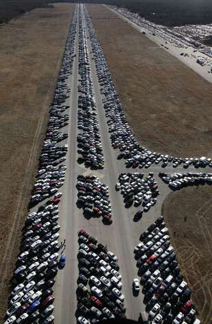 This file photo shows thousands of cars that were damaged in Superstorm Sandy and stored on the runways at Calverton Executive Airpark in Calverton, N.Y. USAA totaled some 4,000 customer vehicles that had been damaged, but officials for the San Antonio-based insurer now admit that some vehicles that had been totaled instead were resold and put back on the road. USAA had earmarked 174 vehicles to be sold for parts only, but has found that some were fraudulently given clean titles. Photo: Associated Press