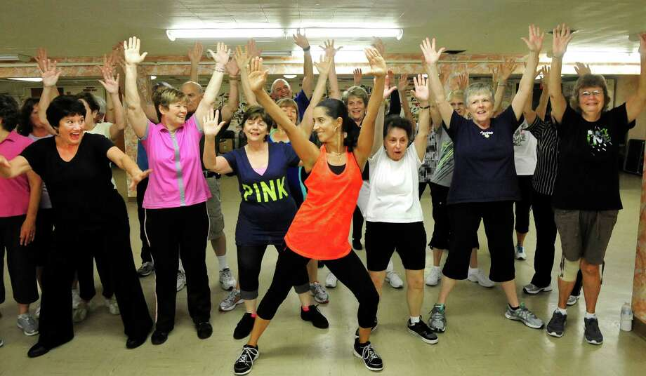 Monica Logan, center, leads a group stretch as the Bethel Senior Center, in Bethel, Conn., offers its first Zumba Gold class on Friday, Sept. 6, 2013. The centers Monday and Wednesday classes proved so popular that a third class has now been added every Friday at 9 a.m. Photo: Michael Duffy / The News-Times