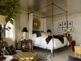 Animal furs and a canopy bed offer a stately ambience, while a bedside table with a distressed finish displays a modern light fixture.Ê