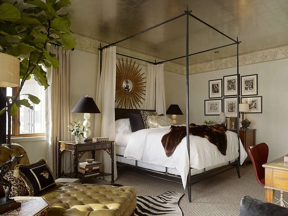 Animal furs and a canopy bed offer a stately ambience, while a bedside table with a distressed finish displays a modern light fixture. Photo: Matthew Millman, © Matthew Millman