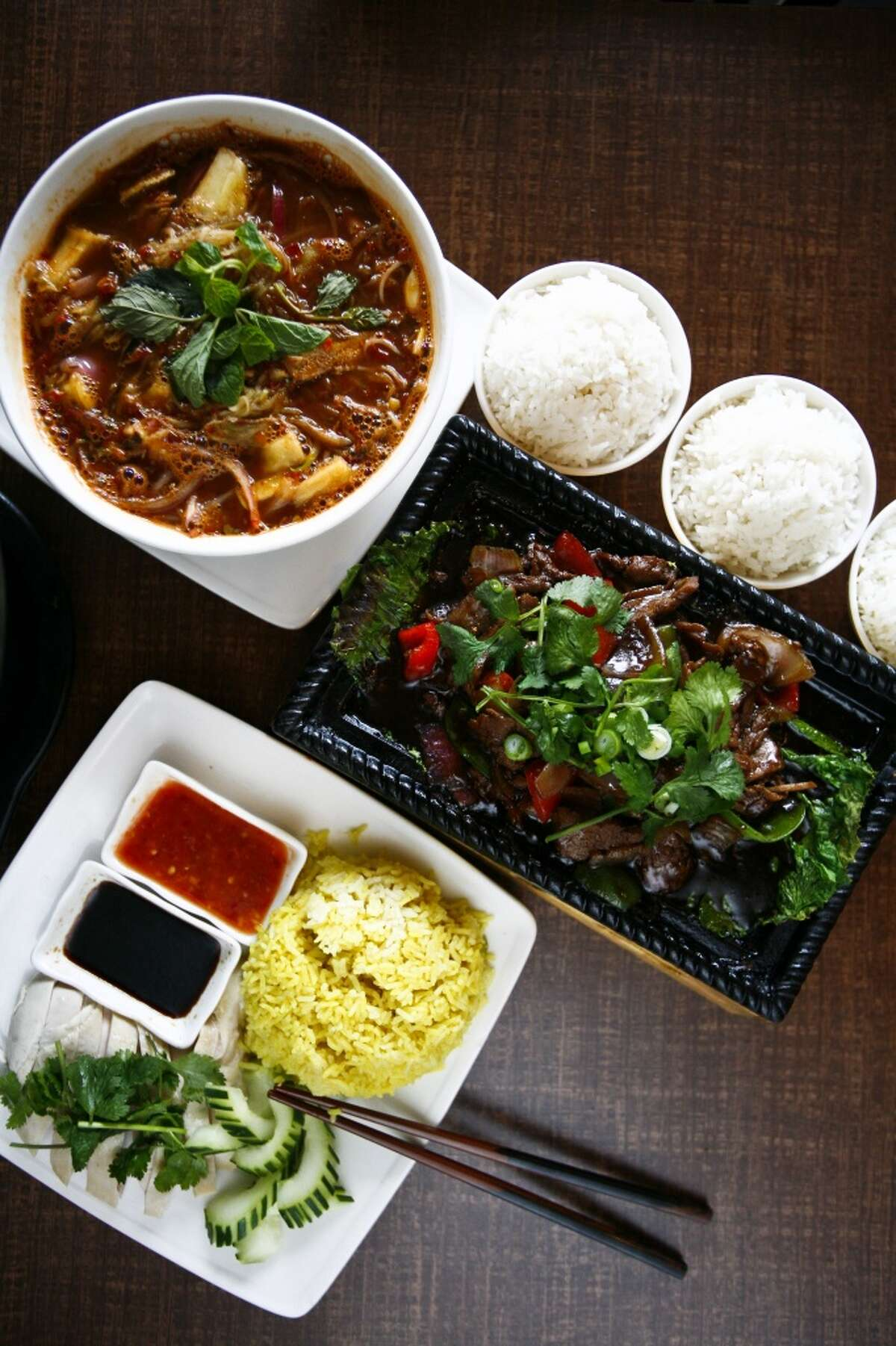 The Penang Assam Laksa noodle soup (top to bottom), the Sizzling Beef With Black Pepper platter and the Hainanese Chicken with Rice dish at Banana Leaf Malaysian Cuisine, 9889 Bellaire.