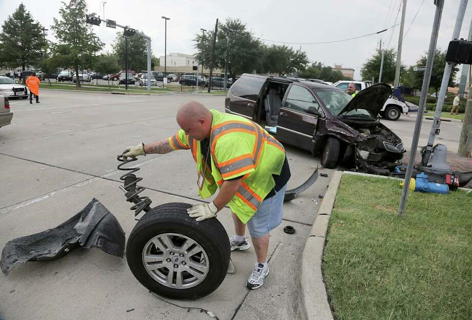 Derek Carter with Autohaus KEH Inc. cleans up car parts from a two-car accident at the intersection of McGowen and Fannin in Houston, Sept. 6, 2013. Multiple people were injured in the accident and transported to an area hospital. (Houston Chronicle) Photo: Thomas B. Shea, For The Chronicle / © 2013 Thomas B. Shea