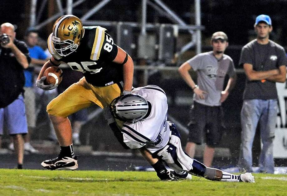 LC-M offensive lineman Matthew Chitty, #85, makes a catch and heads down the field dragging WO-Sdefensive end Grant LaPoint-Teate during the Little Cypress-Mauriceville High School football game against West Orange-Stark High School football game in Orange on Friday, August 30, 2013. Photo taken: Randy Edwards/The Enterprise Photo: Beaumont Enterprise